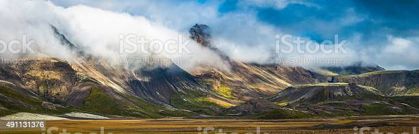 Photo of Clouds rolling over dramatic mountain panorama to valley below Iceland