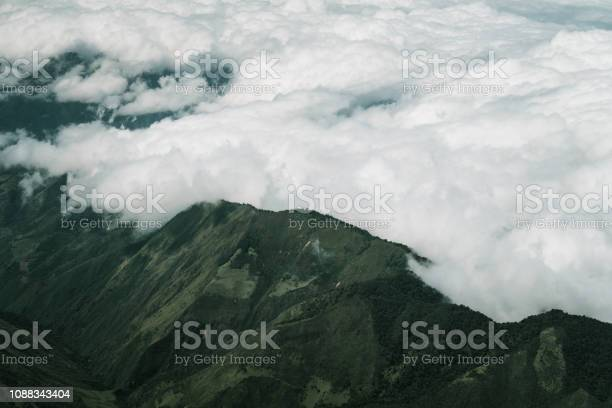 Photo of Clouds rolling over mountain peaks near Quito