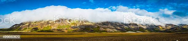 Photo of Clouds rolling over mountain ridge panorama to valley below Iceland