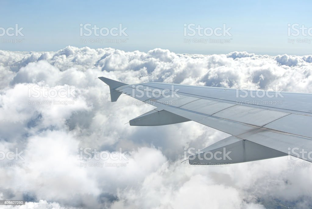 Clouds under the wing of an airplane stock photo