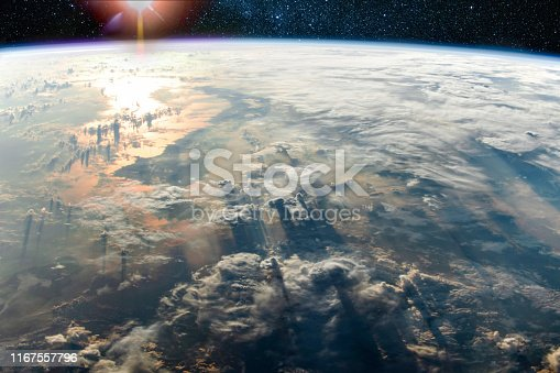 Clouds with long shadows above the Earth and sunlight reflection in the sea, Elements of this image furnished by NASA.  /urls: https://images.nasa.gov/details-iss013e78960.html https://images.nasa.gov/details-iss060e022358.html https://earthobservatory.nasa.gov/images/145363/cloudy-sulawesi