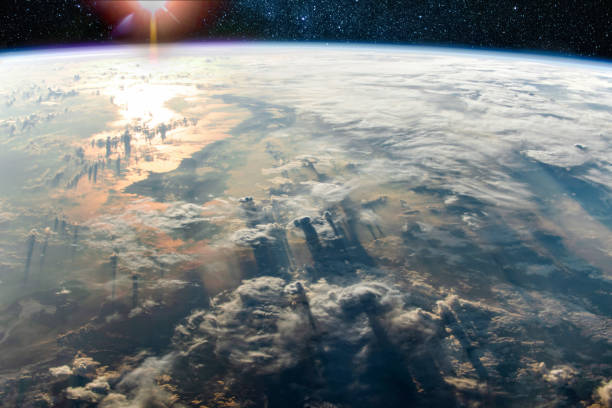Clouds with long shadows above the Earth and sunlight reflection in the sea, Elements of this image furnished by NASA.