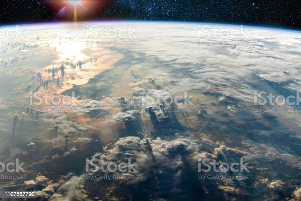 Photo of Clouds with long shadows above the Earth and sunlight reflection in the sea, Elements of this image furnished by NASA.
