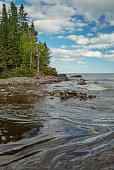 Wave pattern, flowing water, cloudscape, pine trees, rocky shore