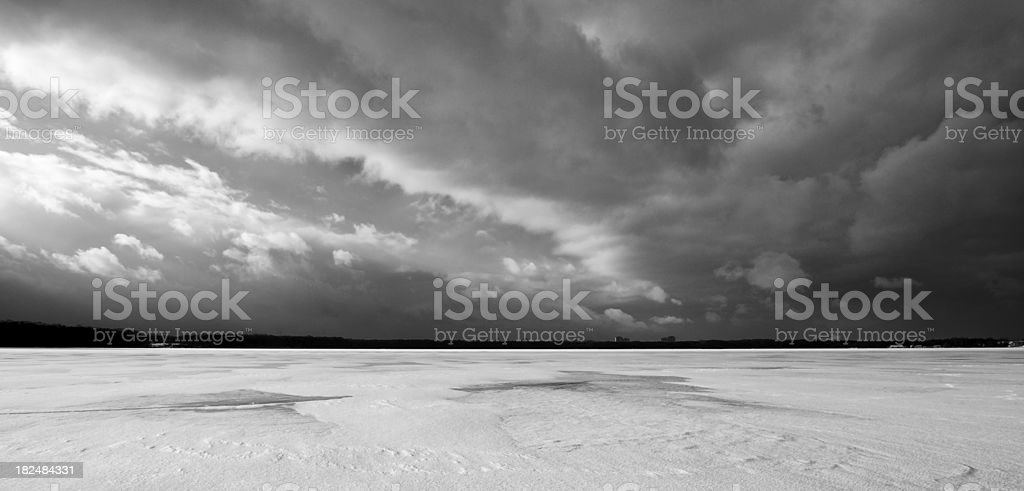 cloudscape over frozen lake, greyscale image stock photo