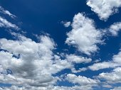 Horizontal landscape photo of fluffy white clouds in a bright blue sky on a sunny day in Summer