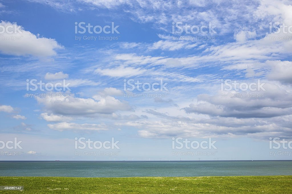 Cloudscape with simple sea and grass foreground composition stock photo