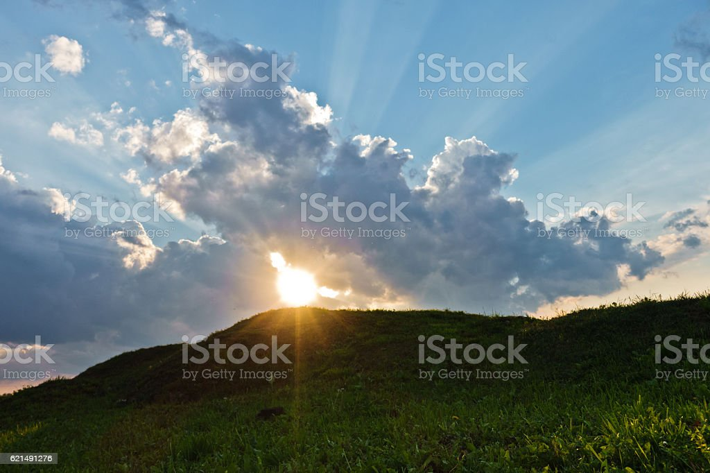Cloudscape with sun rays over small green hills Lizenzfreies stock-foto