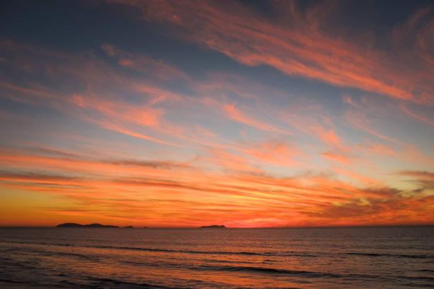 un tramonto nuvoloso e colorato sulla costa pacifica del messico - tramonto foto e immagini stock