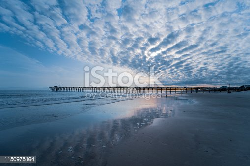 A long beach fishing pier on the horizon with beautiful spattered clouds.