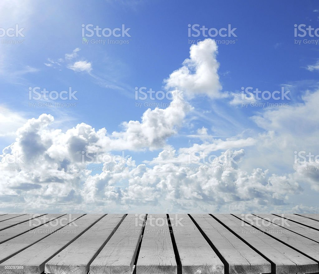 Cloudy blue sky with wooden platform stock photo