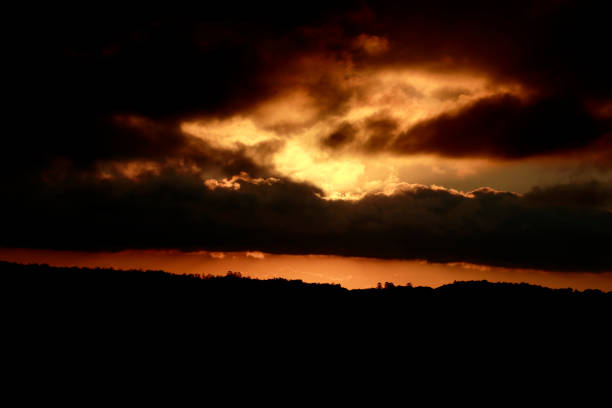 Cloudy Rural Sunset with Hills and Trees Silhouetted stock photo