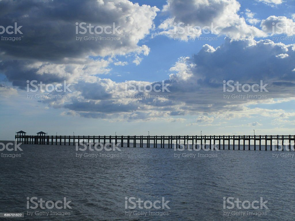 Cloudy skies over pier royalty-free stock photo