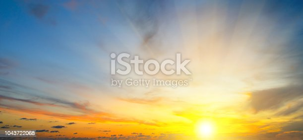 Cloudy sky and bright sun rise over the horizon. Wide photo.