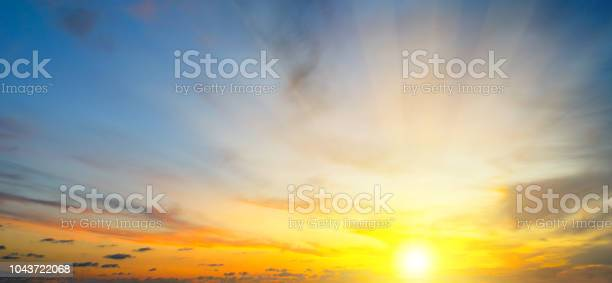 Photo of Cloudy sky and bright sun rise over the horizon.