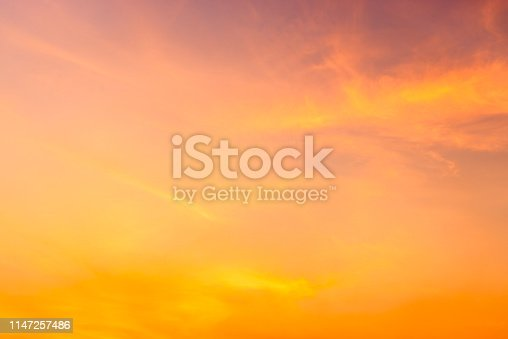 Cloudy sky and orange light of the sun through the clouds with copy space