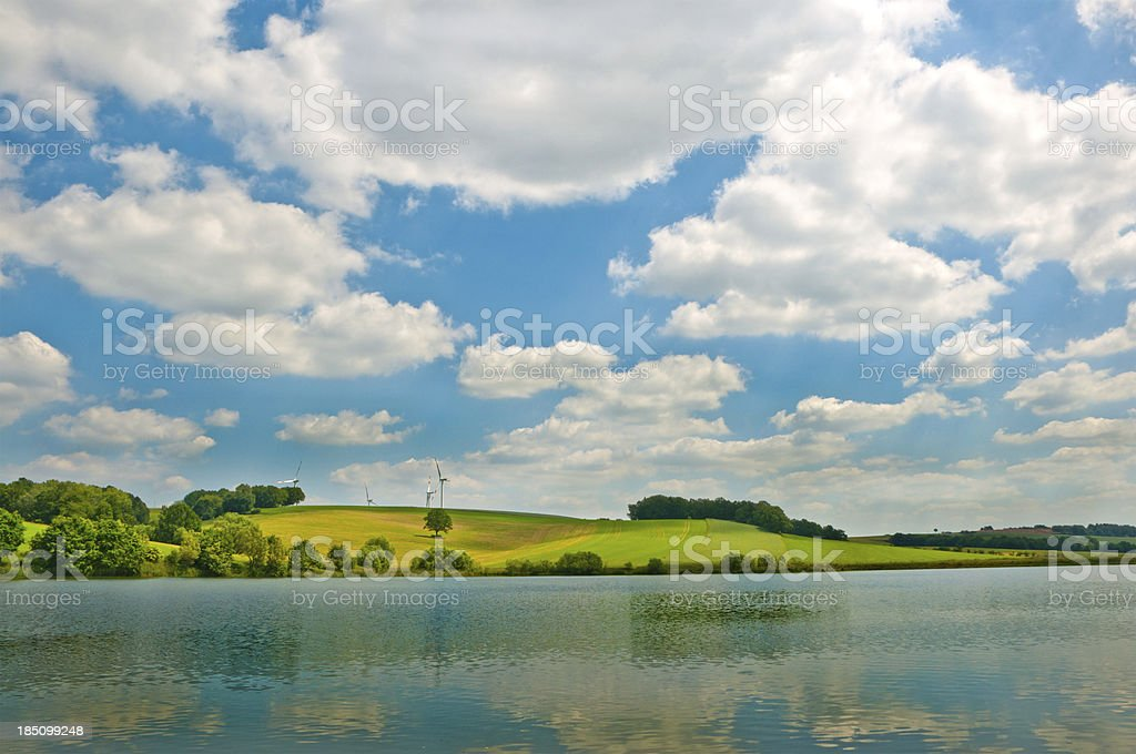 cloudy sky over a lake and rolling hills stock photo
