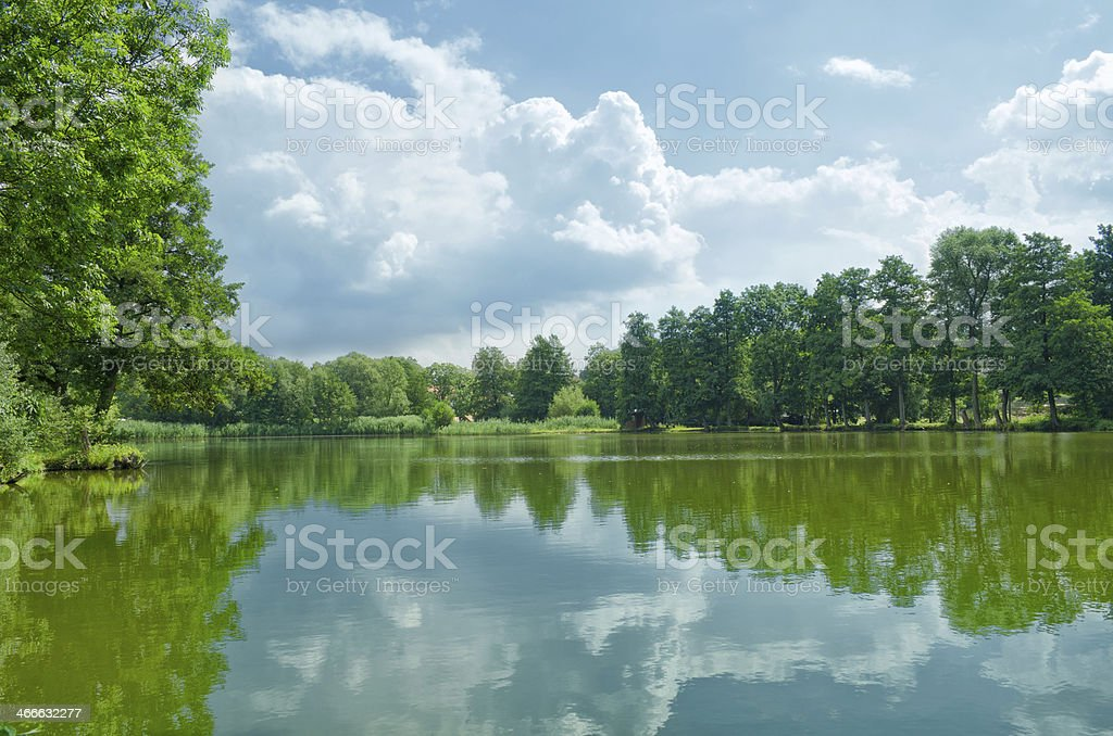 cloudy sky over a village pond stock photo