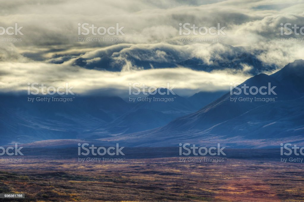 A cloudy skyscape hangs over a valley in Denali National Park. stock photo