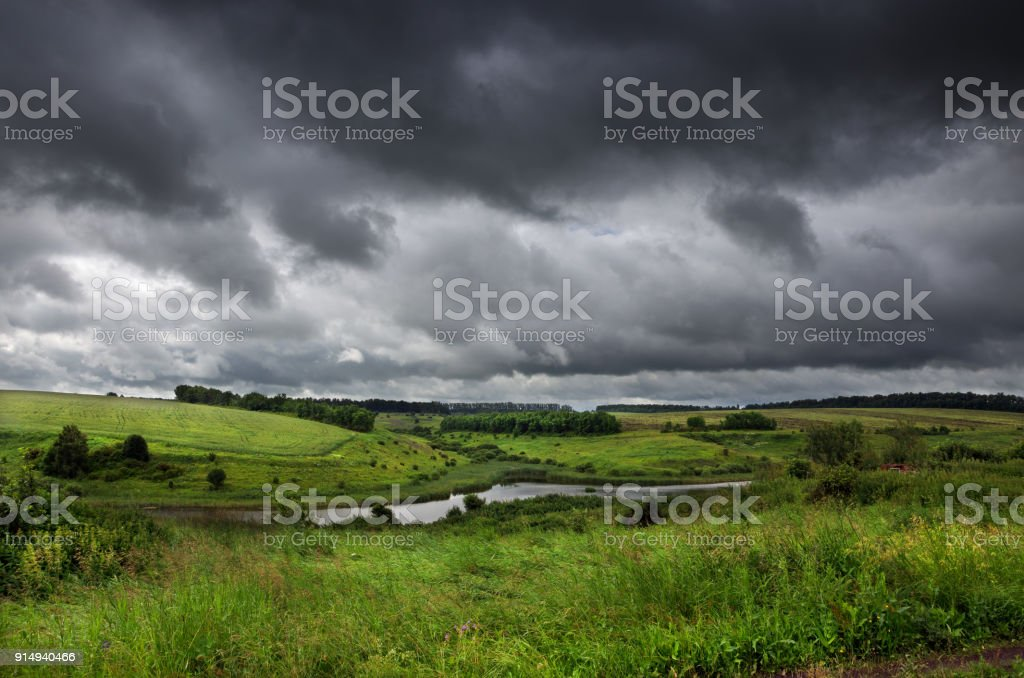 Cloudy summer landscape with small river.Dark stormy clouds in dramatic overcast sky.Fields,green meadows and woods. - foto stock