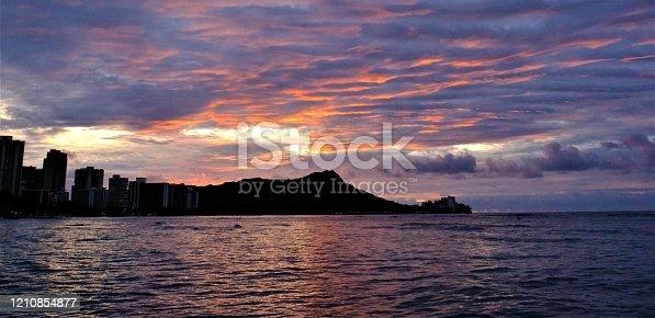 Cloudy sunrise at Waikiki beach over Hawaii's famous Diamond Head.  Sun silhouetted the shape of Diamond Head and some hotels on Waikiki Beach.