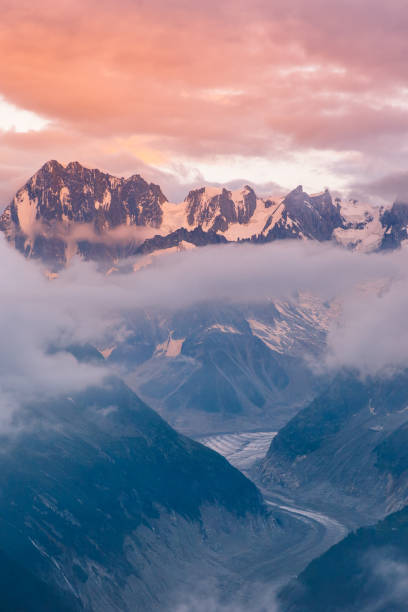 cloudy sunset over iconic mont-blanc mountains range and glaciers - monte bianco foto e immagini stock