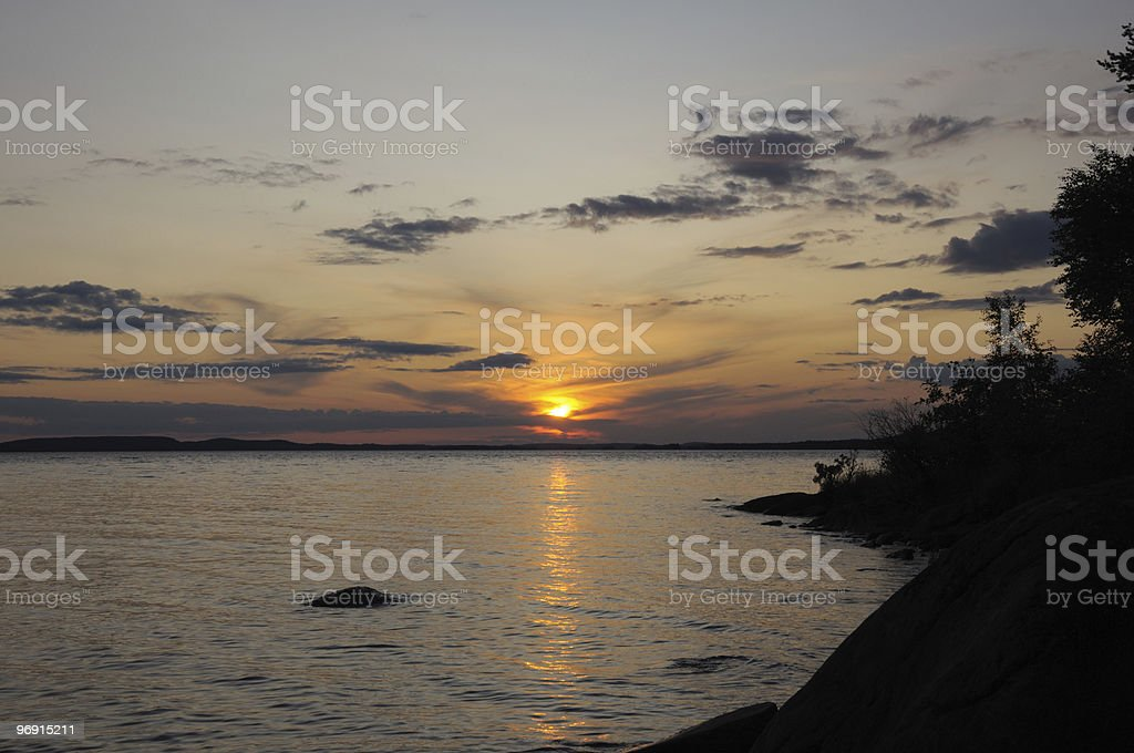 Cloudy sunset over lake near island royalty-free stock photo