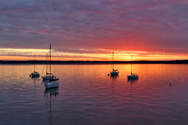 Cloudy sunset over the lake. Amazing summer landscape with colorful sunset sky reflected in the water with drifting yachts on the lake Mendota, city of Madison, Wisconsin, Midwest USA. dane county stock pictures, royalty-free photos & images