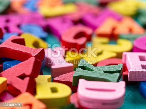 istock clouseup of colorful wooden alphabet on green background. 1054692490