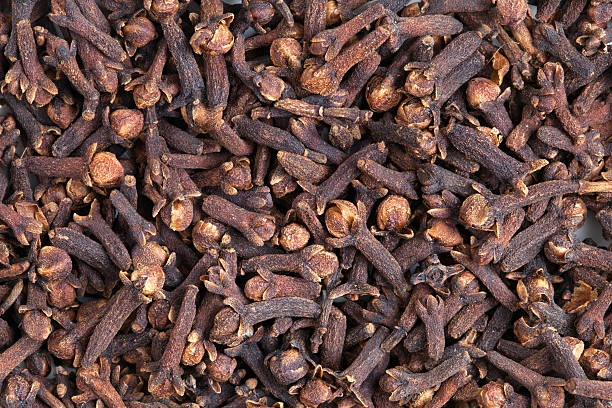 Clove (Syzygium aromaticum) Clove (Syzygium aromaticum) texture, background. Used as a spice in cuisines all over the world. The plant is also used in medicine. clove spice stock pictures, royalty-free photos & images