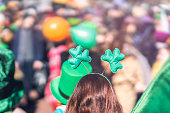 Clover head decoration on head of girl close-up. Saint Patricks day, parade in the city, selectriv focus, copy space