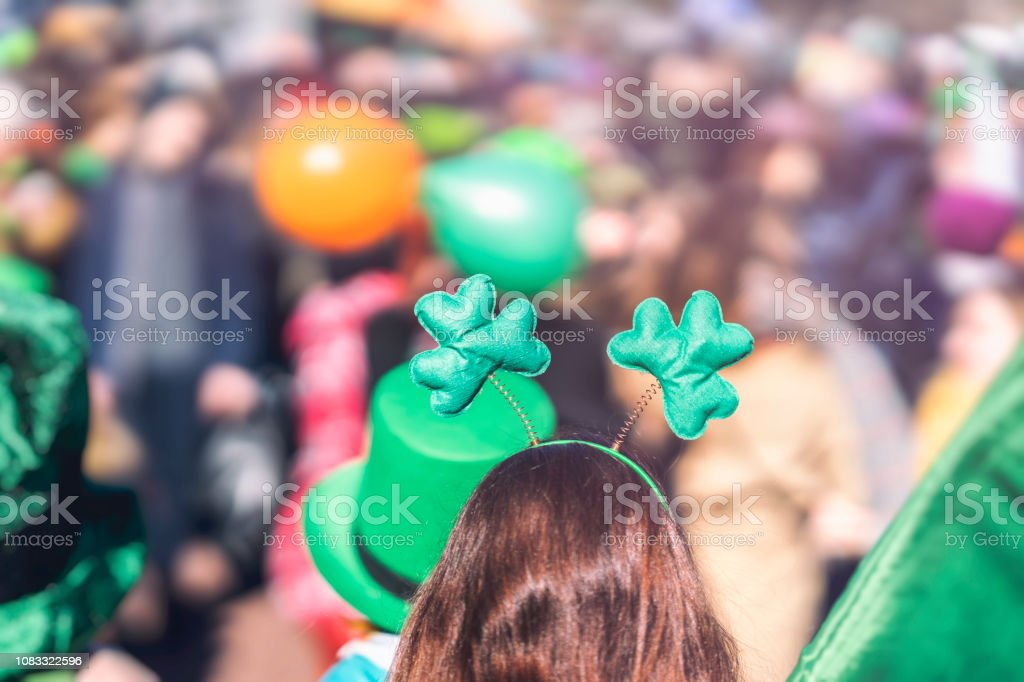 Clover head decoration on head of girl close-up. Saint Patrick day, parade in the city, selectriv focus stock photo