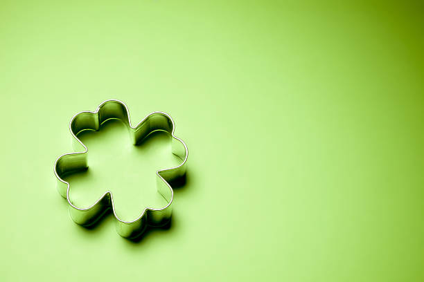 clover pastry cutter on green poster board - st patricks day food stock photos and pictures