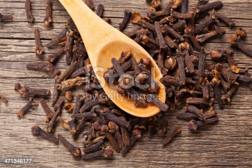 Closeup of cloves in wooden teaspoon on wooden background; Adobe RGB color space;
