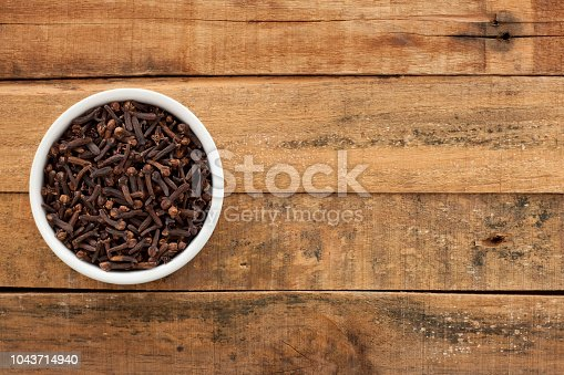 Top view of white bowl full of cloves over wooden table