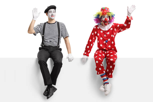 Clown and a mime sitting on a panel and waving stock photo