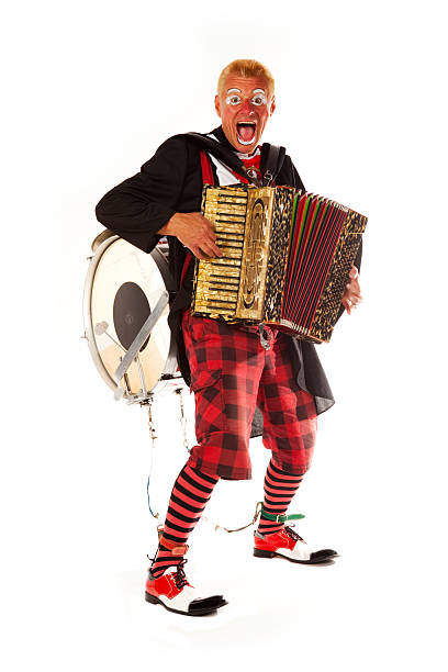 Clown doing tricks with accordion and drum on his back stock photo