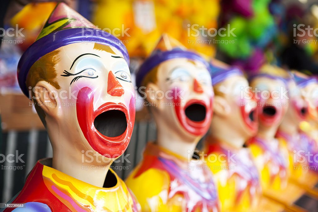 A carnival game with a line of clowns with open mouths ready for...