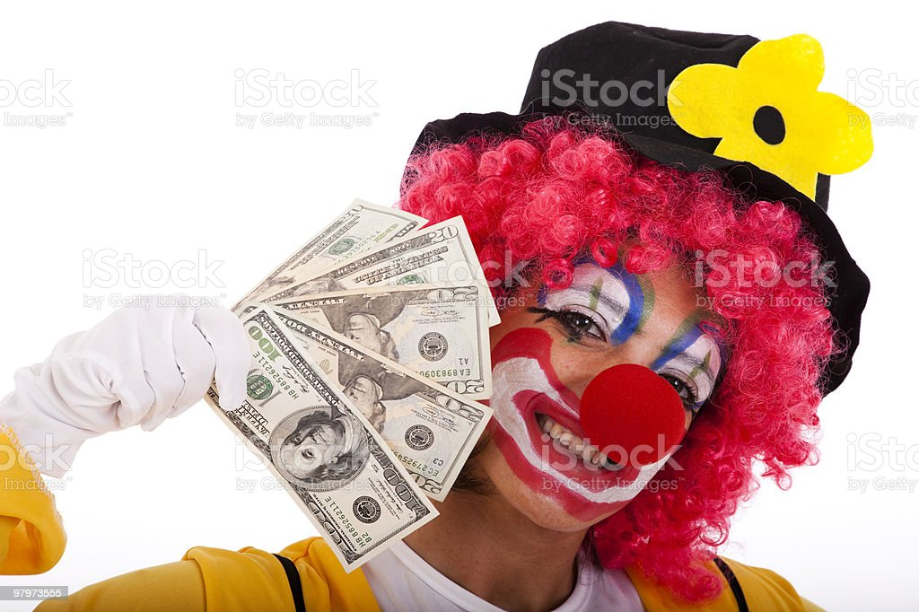 A clown holding up a fan of money royalty-free stock photo