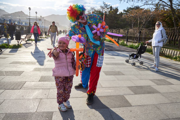 Clown in bright multi-colored clothes gave the cute child a balloon flower stock photo