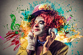Woman dressed as a colorful clown listening to music with colorful illustrations