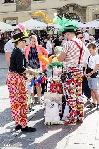 Clowns making animals with balloons at the Square Market (Rynek Główny) downtown Krakow , Poland during summer day