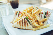 Close up of a white saucer with club sandwich with French fries