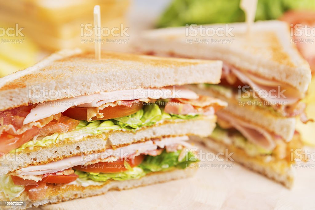 Club sandwich on a rustic table in bright light stock photo