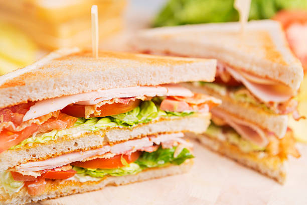 club sandwich on a rustic table in bright light - club sandwich stock photos and pictures
