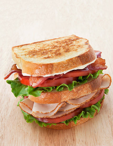 club sandwich on a wooden cutting board. - club sandwich stock photos and pictures