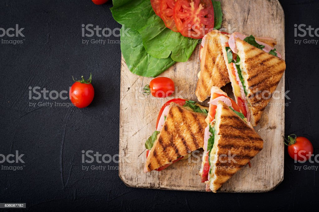 Club sandwich panini with ham, tomato, cheese and basil. Flat lay. Top view stock photo