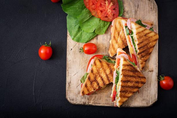 club sandwich panini with ham, tomato, cheese and basil. flat lay. top view - panino ripieno foto e immagini stock