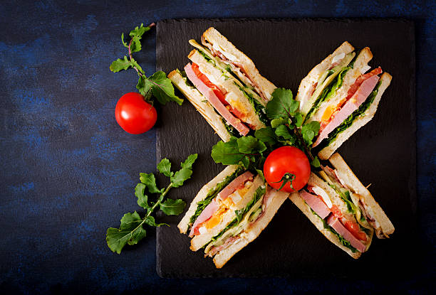 club sandwich with ham, bacon, tomato, cucumber, cheese, eggs - französischer zwiebel dip stock-fotos und bilder