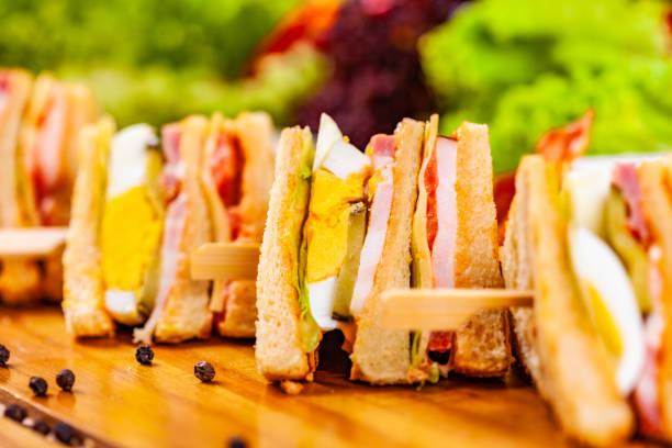 club-sandwiches mit ei, schinken, speck, gemüse auf holzschnittbrett - käse wurst salat stock-fotos und bilder